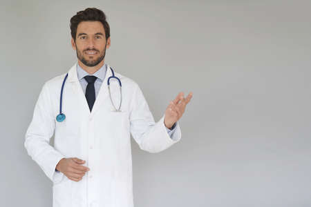 Smiling doctor standing on grey background Фото со стока