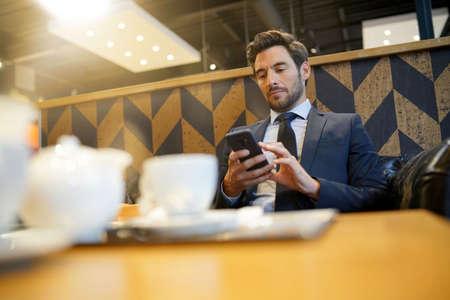 Businessman using smartphone at airport waiting room