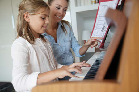 Little girl taking piano lesson, teacher watching her
