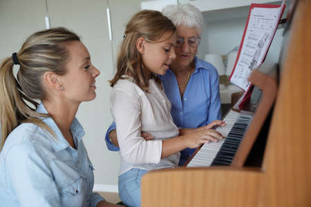 Little girl playing the piano, mom and grandma watching her