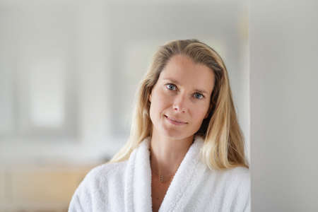 Blond woman wearing white bathrobe Banque d'images