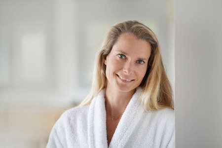 Blond woman wearing white bathrobe