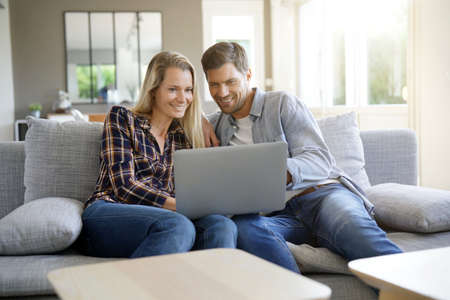 Cheerful couple at home using laptop