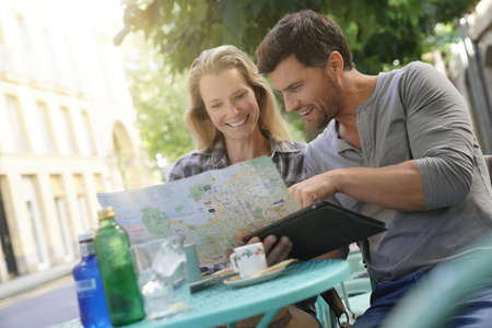 Tourists sitting at coffee shop table reading map