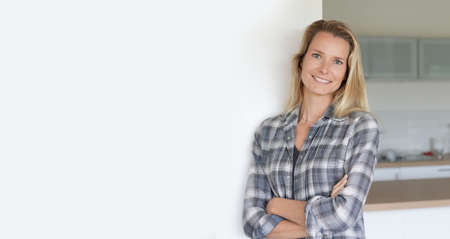 Attractive blond woman standing at home, copyspace