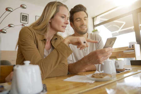 Young couple looking at a cell phone in a coffee shop Banque d'images
