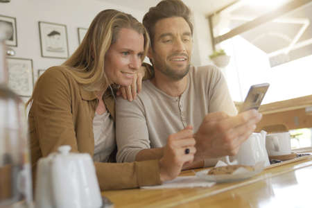 Young couple looking at a cell phone in a coffee shop