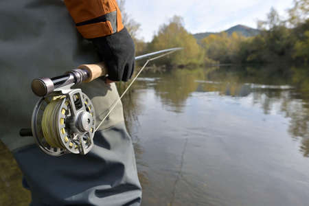 fly fisherman in river in autumn