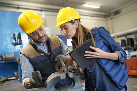 Mechanical workshop manager giving instructions to employee Reklamní fotografie
