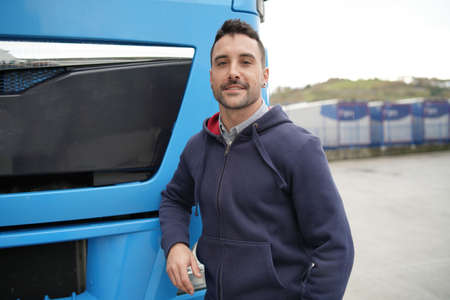 Truck driver standing in front of lorry Stock Photo