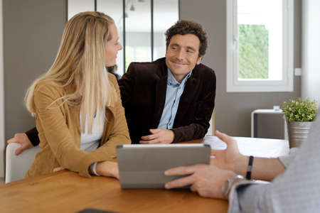 Businessman showing real-estate project to couple of clients
