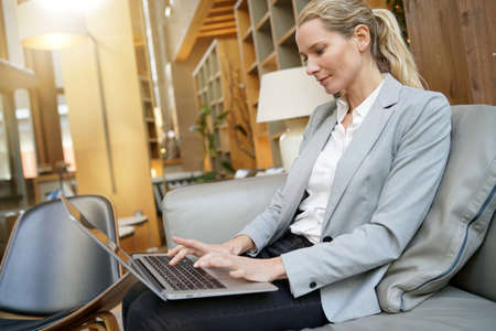 Businesswoman working on laptop in hotel lounge