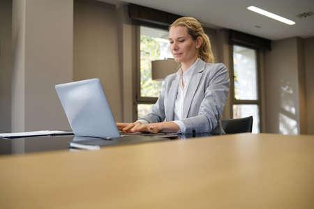 Businesswoman working on laptop in modern office 免版税图像