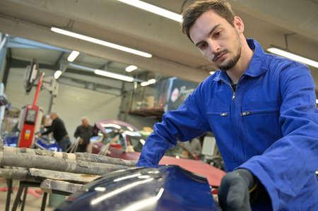 Apprentice working on car engine in workshop