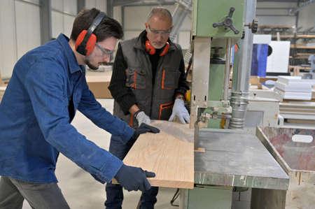 Carpenter with apprentice working in workshop Stock fotó