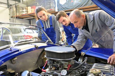 Istruttore con tirocinanti che lavorano sul motore dell'auto