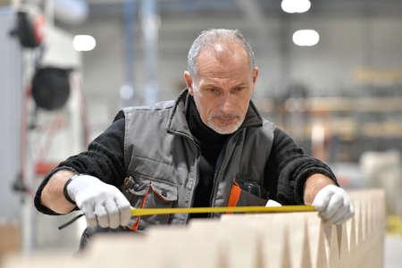Carpenter measuring wood pieces in workshop