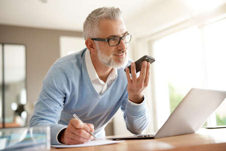 Man in office working on laptop computer and using smartphone