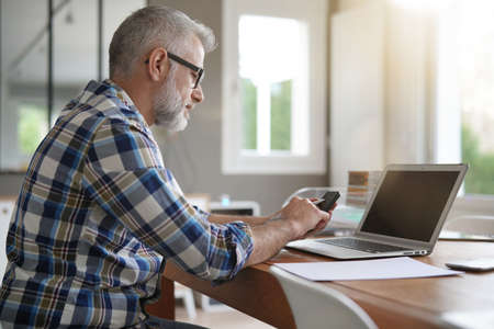 Man working from home with laptop and smartphone