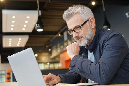 Salesman in restaurant working on laptop computer Reklamní fotografie
