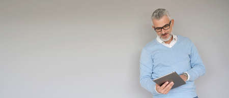 Middle-aged man using tablet, isolated on grey background - template