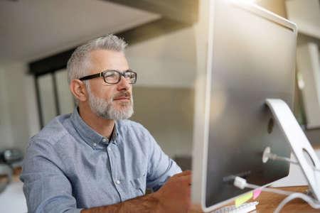 Man in office working on desktop computer