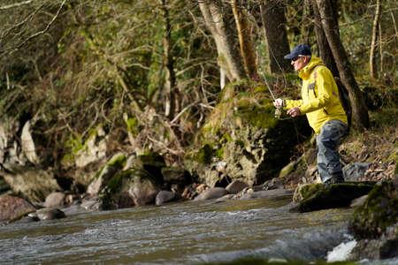 pêcheur à la mouche en rivière en hiver Banque d'images