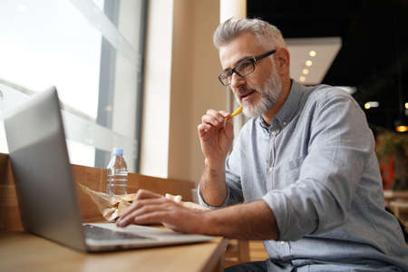Man having lunch in front of laptop