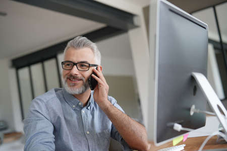 Mature man in office talking on phone