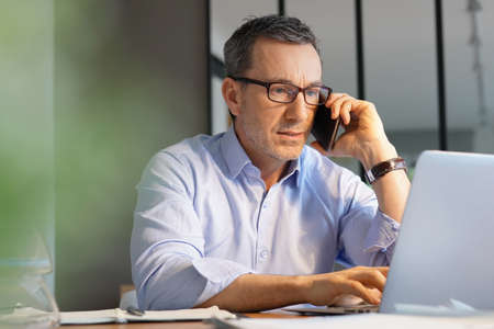 Business manager working in office talking on phone