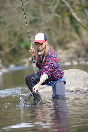 woman catching rainbow trout fly in river Imagens