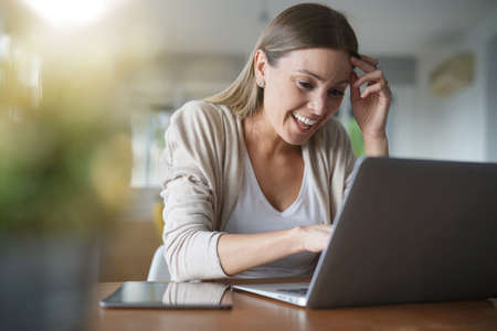 Cheerful young woman at home connected with laptop