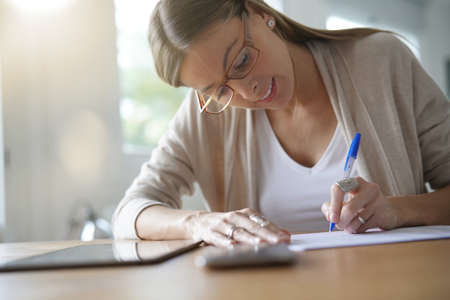 Portrait of woman writing on document
