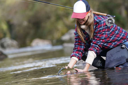 woman catching rainbow trout fly in river