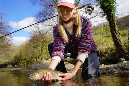Woman catching rainbow trout fly in river Banque d'images