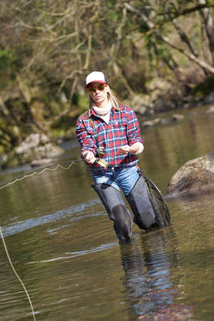 Woman fly fishing in river Banque d'images