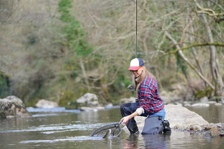 Woman catching rainbow trout fly in river Banco de Imagens