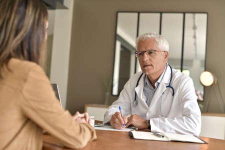 Doctor attending patient in office Фото со стока