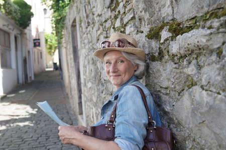 Portrait of senior woman visiting touristic town