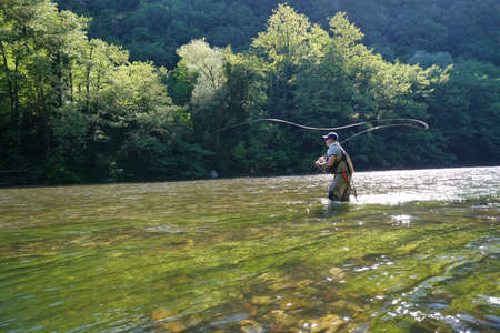 fly trout fisherman in big river
