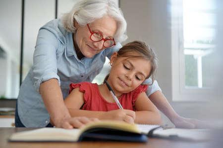 grandmother helping grandkid with homework Foto de archivo