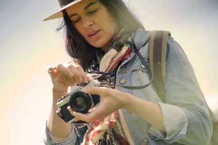Portrait of dark-haired woman with hat taking pictures with vintage camera 스톡 콘텐츠
