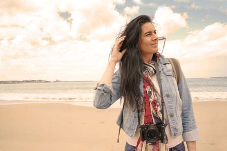 trendy dark-haired woman standing by the beach