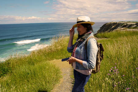 Woman walking by the ocean coast, wearing hat and using smartphone