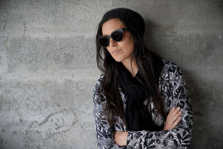 trendy woman wearing black sunglasses and scarf standing on concrete wall, isolated 스톡 콘텐츠
