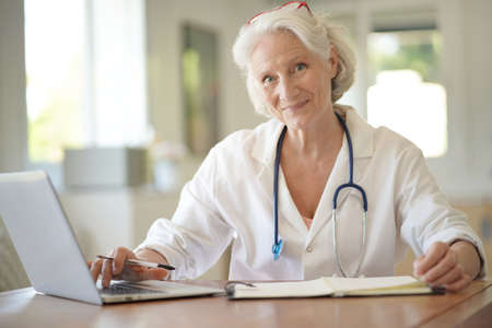 Portrait of smiling senior woman doctor with white hair, working on laptop