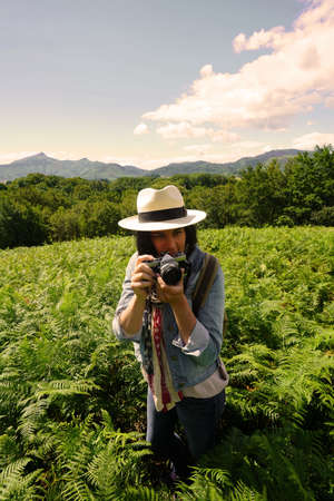 Woman with hat taking pictures in beautiful and natural landscape 스톡 콘텐츠