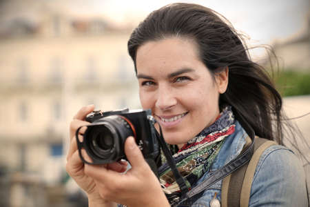 Portrait of woman reporter taking pictures with reflex camera 스톡 콘텐츠