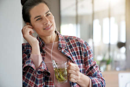 Beautiful 40-year-old woman at home with earphones on, drinking herbal tea