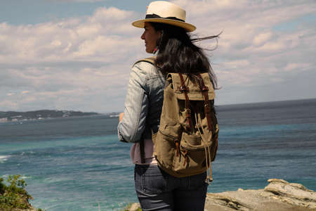 Woman with hat walking by the ocean coast, admiring the scenery 스톡 콘텐츠